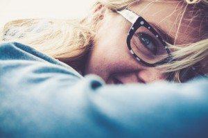 Een foto van een liggende vrouw met een gelukkige uitstraling.