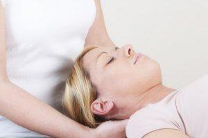 Een afbeelding van een vrouw die een nekmassage krijgt van een fysiotherapeute.