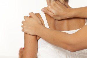 Een foto waarop te zien is dat de schouder van een vrouw gekraakt wordt door een chiropractor.