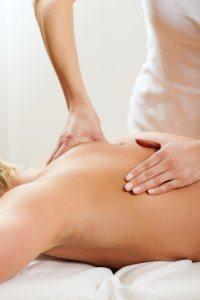 Een afbeelding van een persoon die een schoudermassage krijgt van een fysiotherapeut.