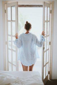 Een afbeelding van een vrouw die openslaande deuren opent in haar slaapkamer.