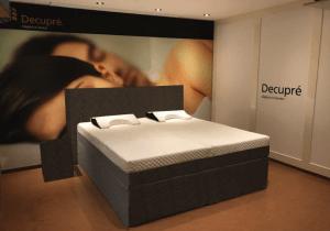 De antraciet grijze Full Core Boxspring set van koudschuim met hoogwaardig multi-layer matras van traagschuim en koudschuim afgebeeld in een showroom.