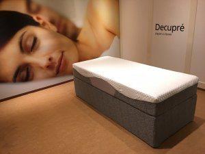 De antraciet grijze eenpersoons Full Core Boxspring van koudschuim met hoogwaardig multi-layer matras van traagschuim en koudschuim afgebeeld in een showroom.