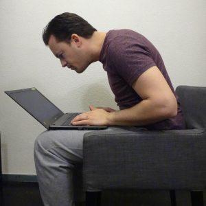 Een foto van een man met nekpijn door een verkeerde lichaamshouding