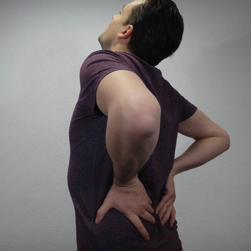Een foto van een man die met zijn handen op zijn rug drukt vanwege rugklachten