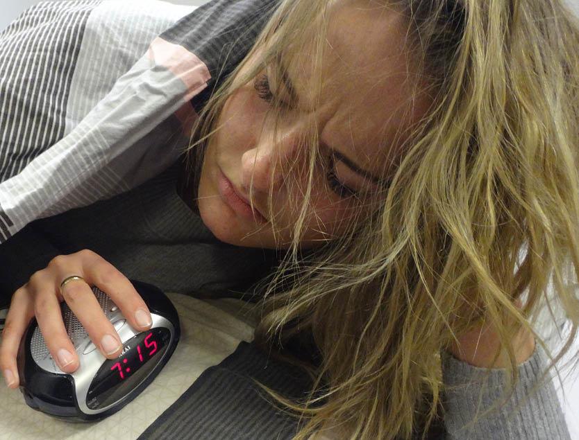 Een foto van een vrouw die vermoeid wakker wordt vanwege slaaptekort