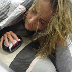 Een foto van een vrouw die geïrriteerd naar haar wekker kijkt door slaaptekort