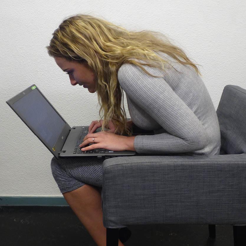 Een foto van een vrouw met een slechte lichaamshouding waardoor rugklachten kunnen ontstaan