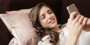 Een foto van een vrouw die haar smartphone in bed gebruikt