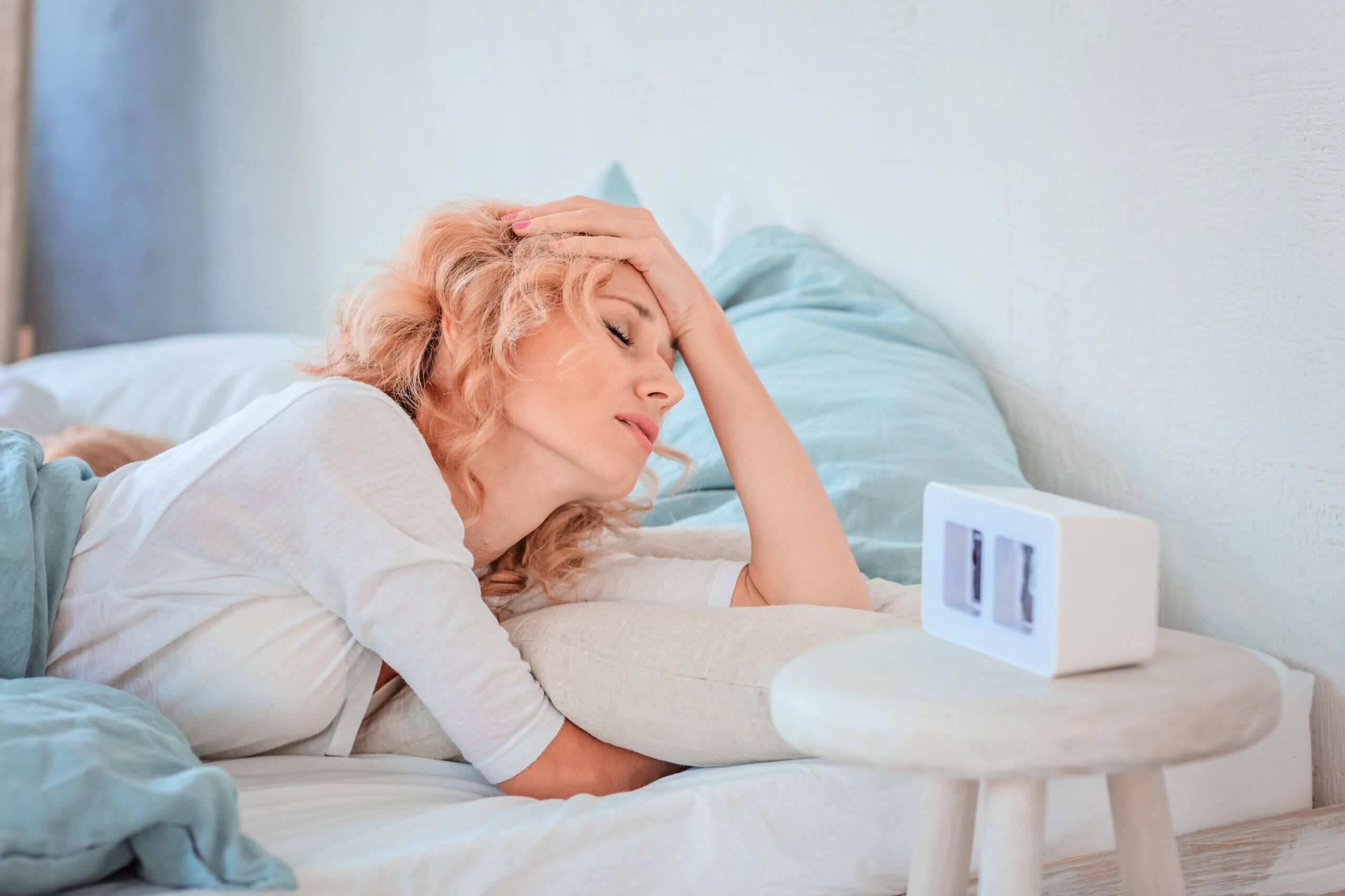 Vrouw vermoeid wakker door wekker