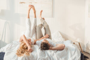 happy couple relaxing in bed and holding hands at morning